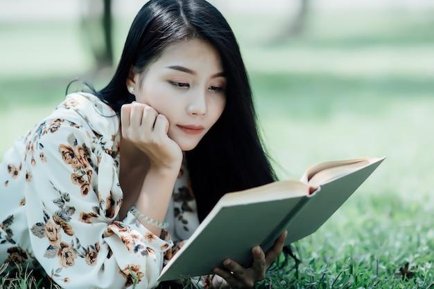 夏の太陽の光で公園で本を読んで美しい少女