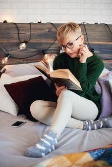 Bella ragazza che legge un libro a letto