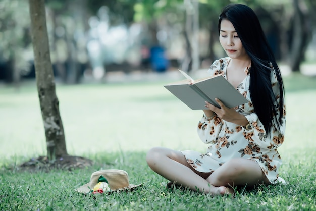 Beautiful girl reading book at park in summer sun light