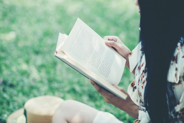 Beautiful girl reading book at park in summer sun light