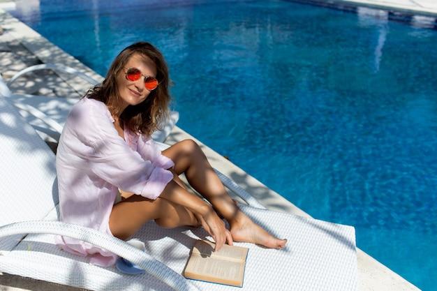 Beautiful girl reads a book near the pool