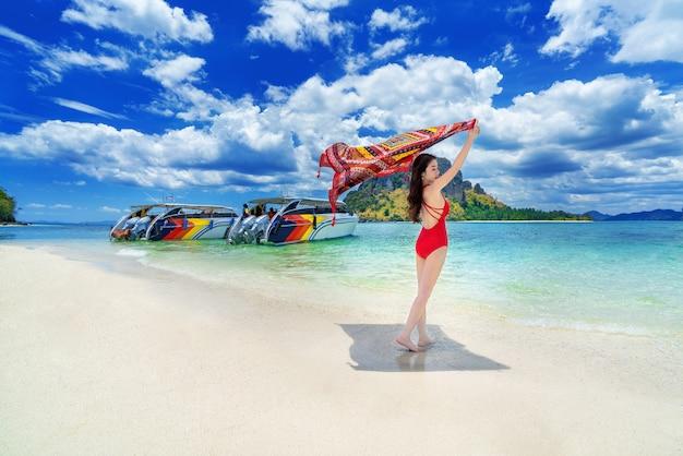 Beautiful girl in red bikini on beach, poda island in thailand.