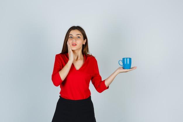 Bella ragazza in camicetta rossa, gonna nera che tiene tazza e sembra scioccata, vista frontale.