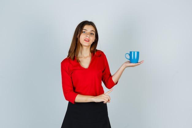 Bella ragazza in camicetta rossa, gonna nera che mostra tazza e guardando premurosa, vista frontale.