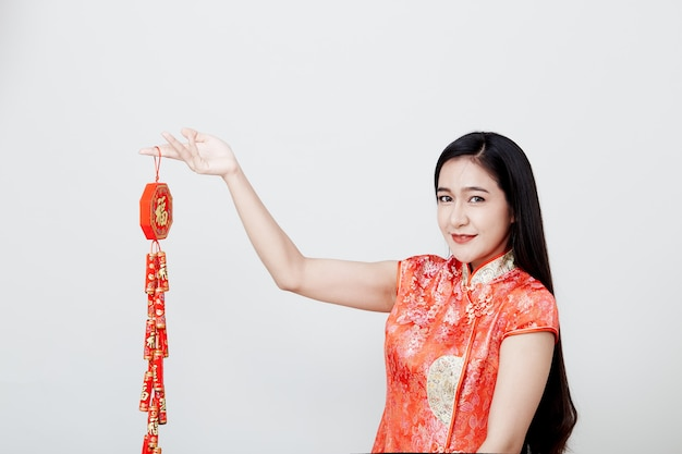 Beautiful girl in red cheongsam holding fire crackers