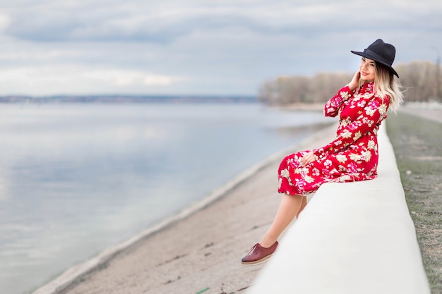 Beautiful girl in a red dress and black hat sits on the waterfront