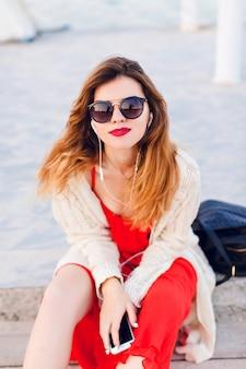 Bella ragazza in vestito rosso e giacca bianca si siede su un molo, sorride e ascolta musica con gli auricolari su uno smartphone.