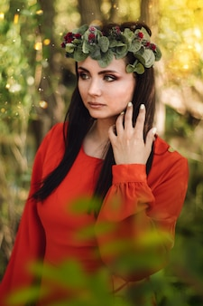 A beautiful girl in a red dress, with long dark hair and a flower wreath on her head walks through the forest.
