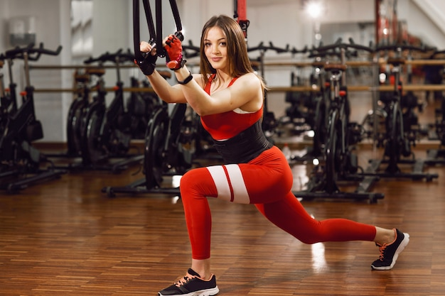 Beautiful girl in a red suit, on the simulator, stretches and trains in the gym