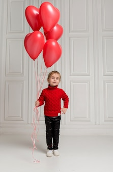 A beautiful girl in a red sweater and leather jeans holds red balloons on a white background with space for text