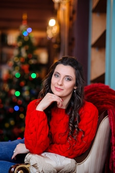 Beautiful girl in a red sweater near the christmas tree.