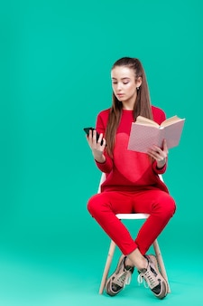 Beautiful girl in red sweater reads book and uses smartphone. choice between technology and books