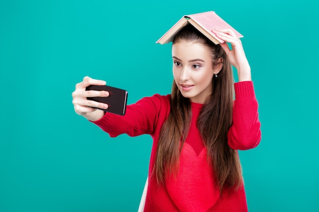 Beautiful girl in a red sweater reads a book and uses a smartphone for selfie
