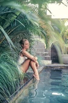 Красивая девушка отдыхает у бассейна в тропическом курорте