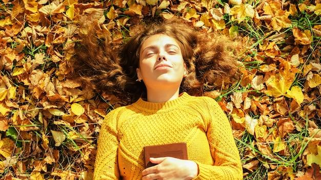 本と秋の公園でリラックスする美しい少女