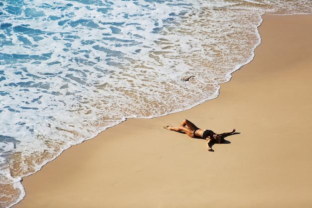 Bella ragazza che si distende sulla spiaggia selvaggia. splendida vista dall'alto.