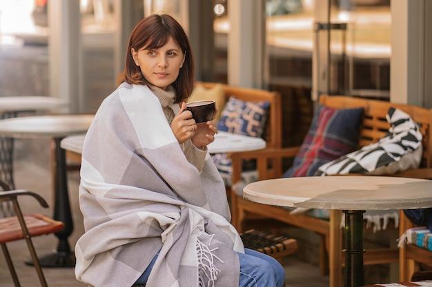 Красивая девушка отдыхает и пьет кофе, сидя в кафе на террасе, завернутый в шерстяное клетчатое одеяло. осеннее утро.