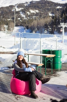 Beautiful girl resting from skiing in a cafe ski resort at the foot of the mountains