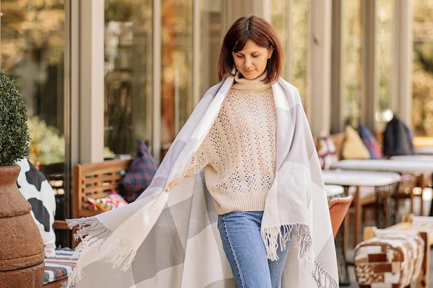 Красивая девушка отдыхает в кафе на террасе, завернувшись в шерстяное клетчатое одеяло. осеннее утро. Premium Фотографии