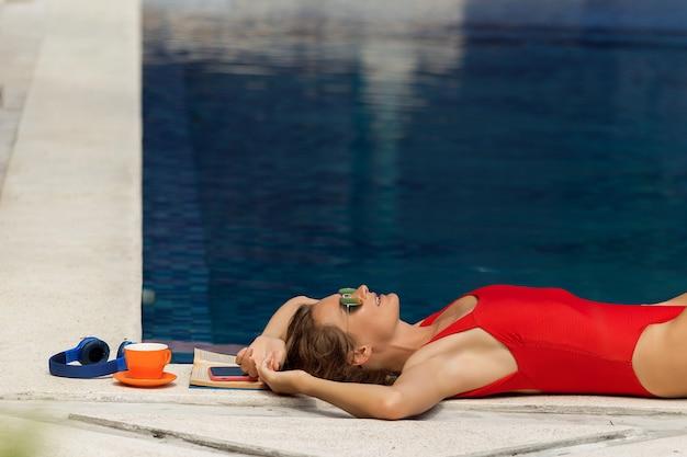 Красивая девушка отдыхает у бассейна