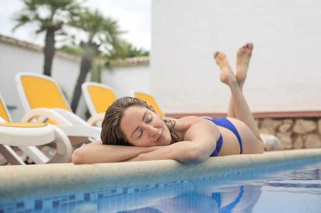 Красивая девушка отдыхает на выступе бассейна