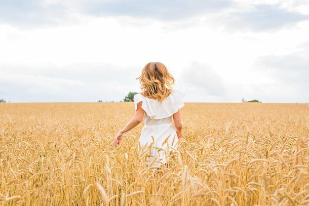 フィールドを実行している美しい少女。自由の概念の背景。