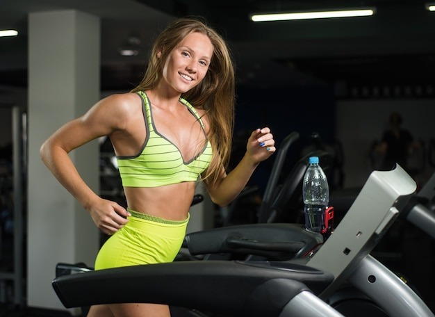 Beautiful girl running on treadmill in gym, healthy lifestyle concept