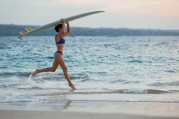 아름다운 소녀는 서핑 보드와 함께 해변을 따라 실행됩니다.