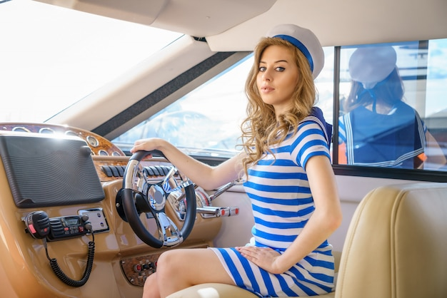 Beautiful girl sailor on a yacht at the helm