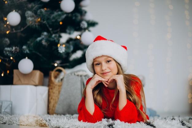 Bella ragazza in santa cappello sotto l'albero di natale