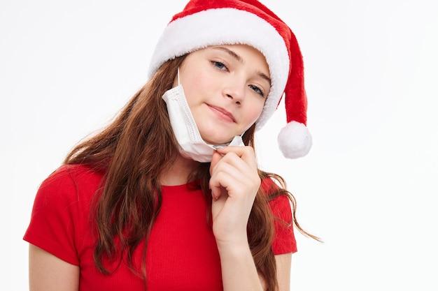 Красивая девушка санта шляпа медицинская маска обрезанный вид. фото высокого качества