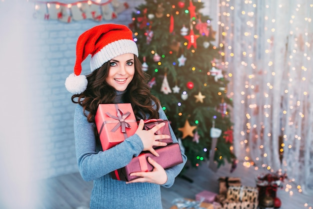 Beautiful girl in santa hat with gift christmas on christmas tree.