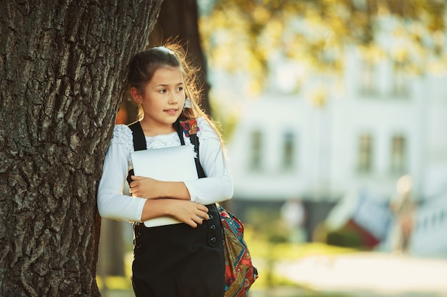 A beautiful girl of school age is standing by a tree and holding a tablet. schoolgirl dressed in a sundress