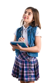 Beautiful girl in school uniform with a notebook in her hand on a white