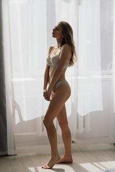 Красивая девушка сексуальная брюнетка в белом нижнем белье позирует в комнате в интерьере студии