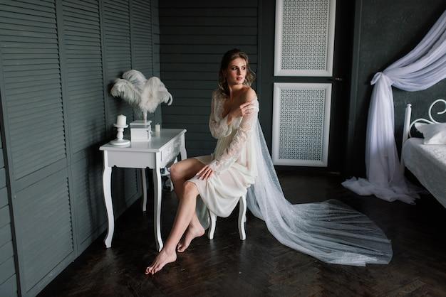 Красивая девушка сексуальная брюнетка в белом нижнем белье позирует в комнате в интерьере