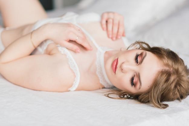 インテリアの部屋でポーズをとって白い下着で美しい少女のセクシーなブルネット