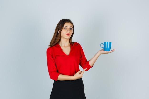 赤いブラウス、黒いスカートと魅力的に見える、正面図でカップを示す美しい少女。