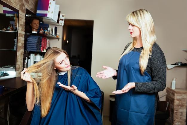 미용사에 그녀의 머리를 보여주는 아름 다운 소녀. 이발소.