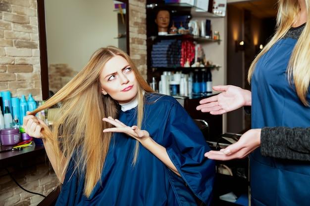 미용사에 그녀의 머리를 보여주는 아름 다운 소녀.
