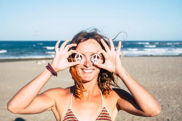 Красивая девушка показывает свой символ мира на глазах, зажатых руками - женщина в бикини на пляже улыбается и смотрит на камеру с солнцем в ее лице