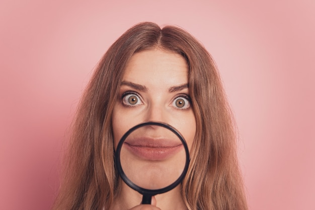 Beautiful girl showing mouth through a magnifying glass