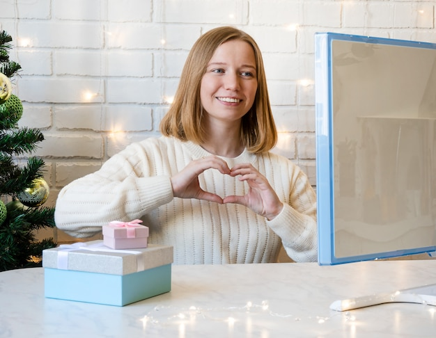 Beautiful girl shows heart symbol with her hands and communicates via the internet in christmas