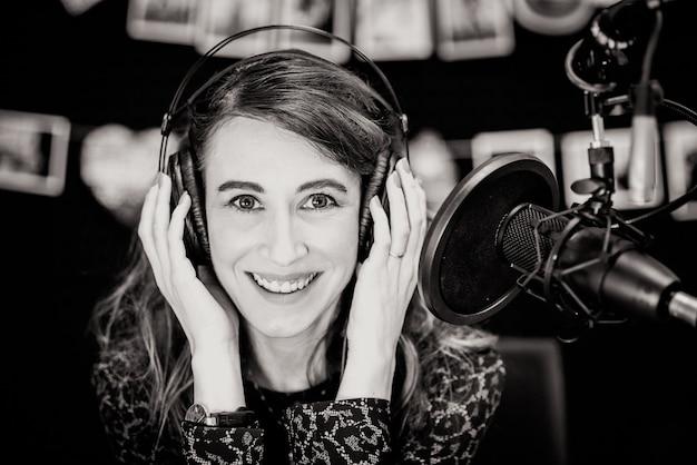 レコーディングスタジオで歌っている美しい少女。