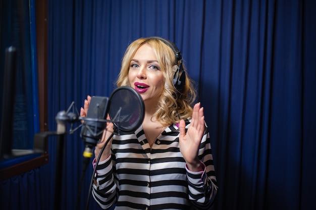 Красивая девушка поет в студии звукозаписи
