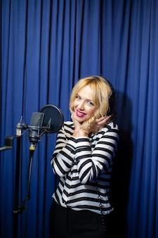 Beautiful girl singing in a recording studio