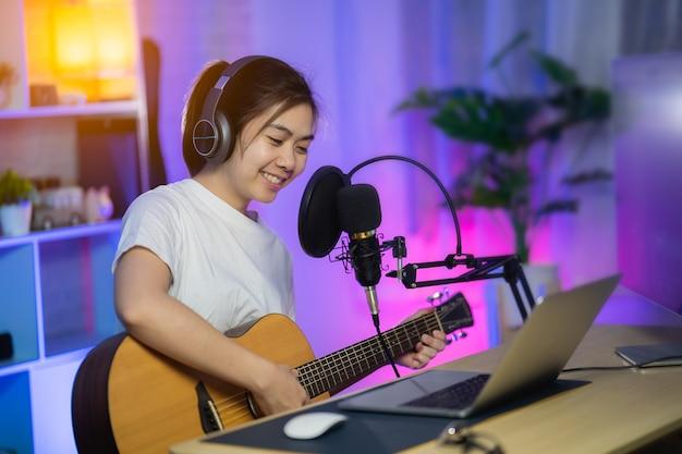 自宅のレコーディングスタジオでヘッドフォンで歌い、マイクで新曲を録音するギターを弾く美少女