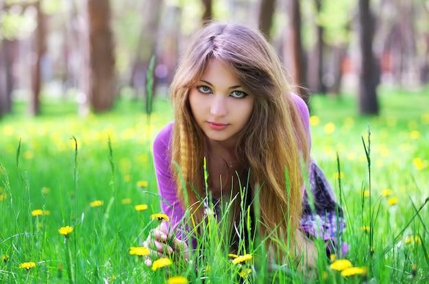 美しい少女は黄色い花と草の上に座る