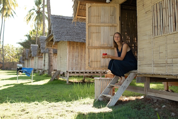 Beautiful girl sits near the bungalow and drinks coffee.