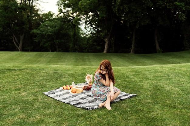 Красивая девушка сидит на одеяле в парке и держит в руках напиток. девушка с веснушками и рыжими волосами на пикнике. экологическая еда. домашние продукты.